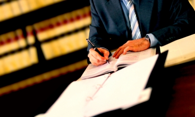 Male divorce lawyer in a suit writing into a booklet with a folder in front of him