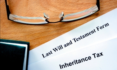 Documents headed last will and testament and inheritance tax on a table next to a pair of glasses