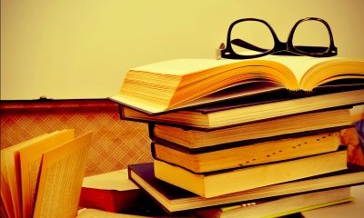 Pile of books with a pair of glasses resting on an open book at the top of the pile