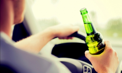 Man sits at steering will of car holding bottle of beer