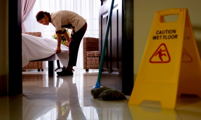 Yellow 'caution wet floor' sign with worker cleaning in the background