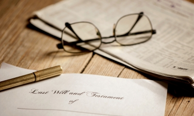 Wooden tabletop with glasses lying on a newspaper and pen lying on a paper with Last Will and Testament written on it