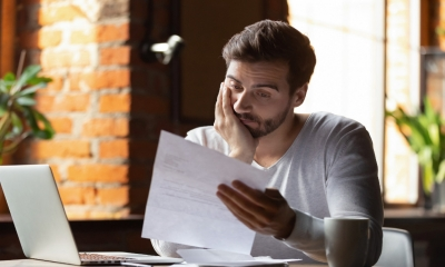 A stressed man reads a debt collection letter and worries about his legal rights.