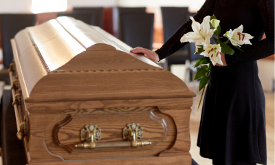 Woman at funeral holding flowers and touching coffin