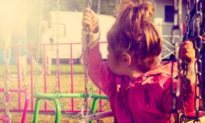 Young girls sits on a swing looking behind her