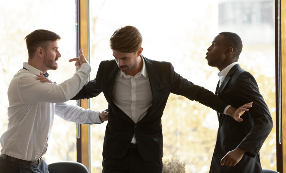 A manager separates two work colleagues who are about to come to blows