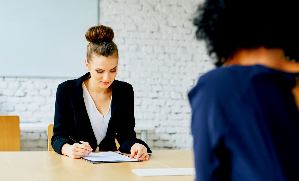 Two women in an HR meeting signing an employment contract - Employment contracts FAQs