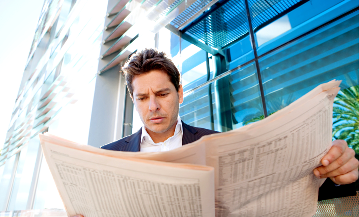Concerned business man checks the latest share prices in the paper