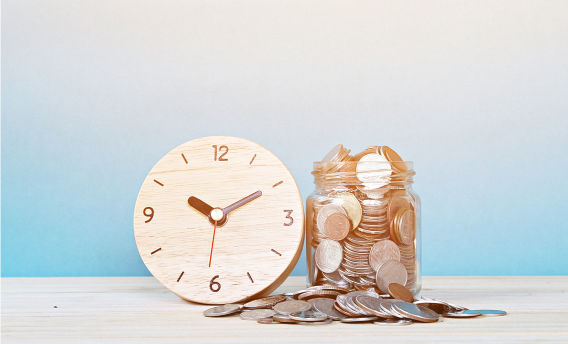 Wooden alarm clock next to a glass jar overflowing with coins