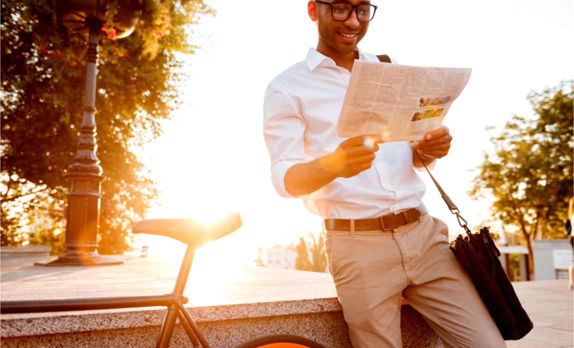 A young, male business person reads the newspaper in the sun.