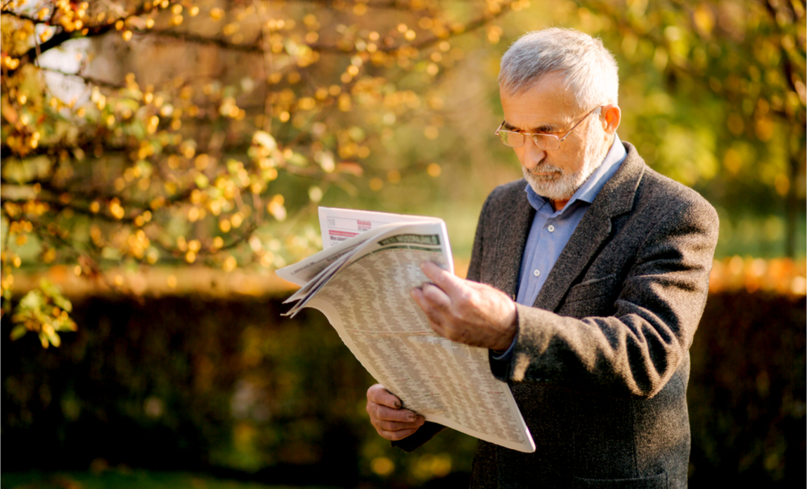 An older man reads a newspaper whilst walking through the park