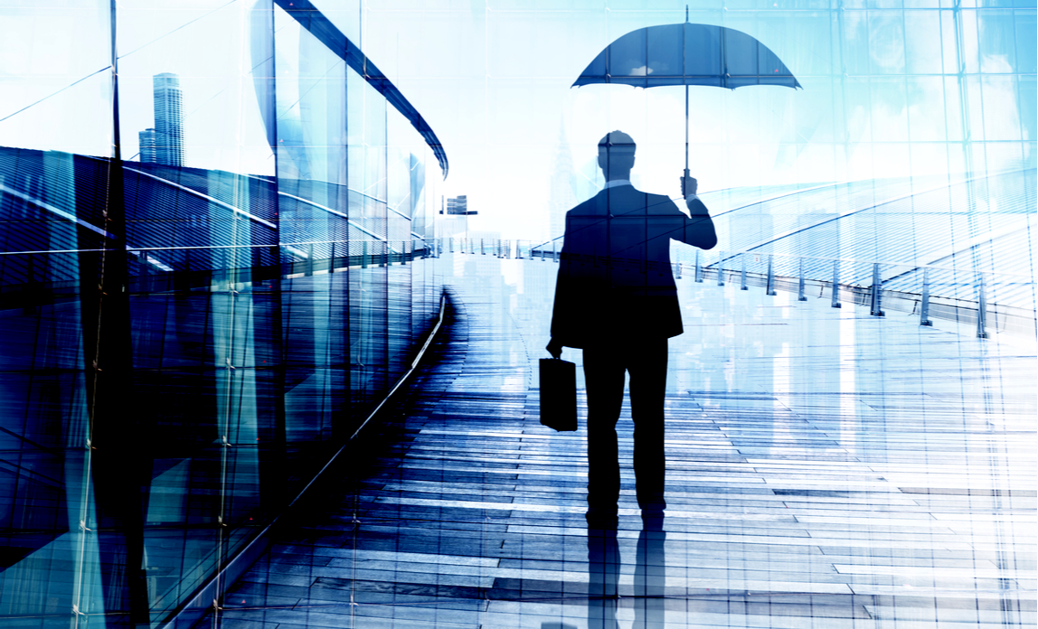 Businessman Standing While Holding an Umbrella