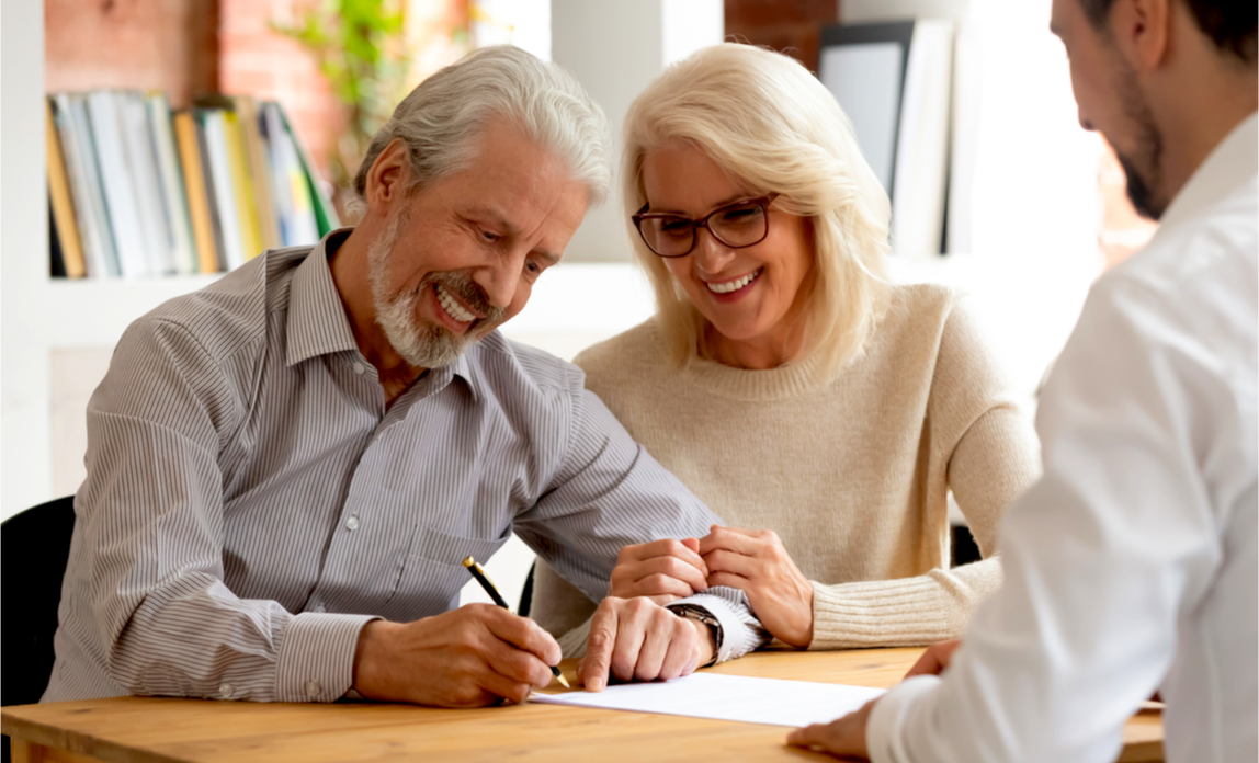 A mature couple sign their Wills after taking expert legal advice