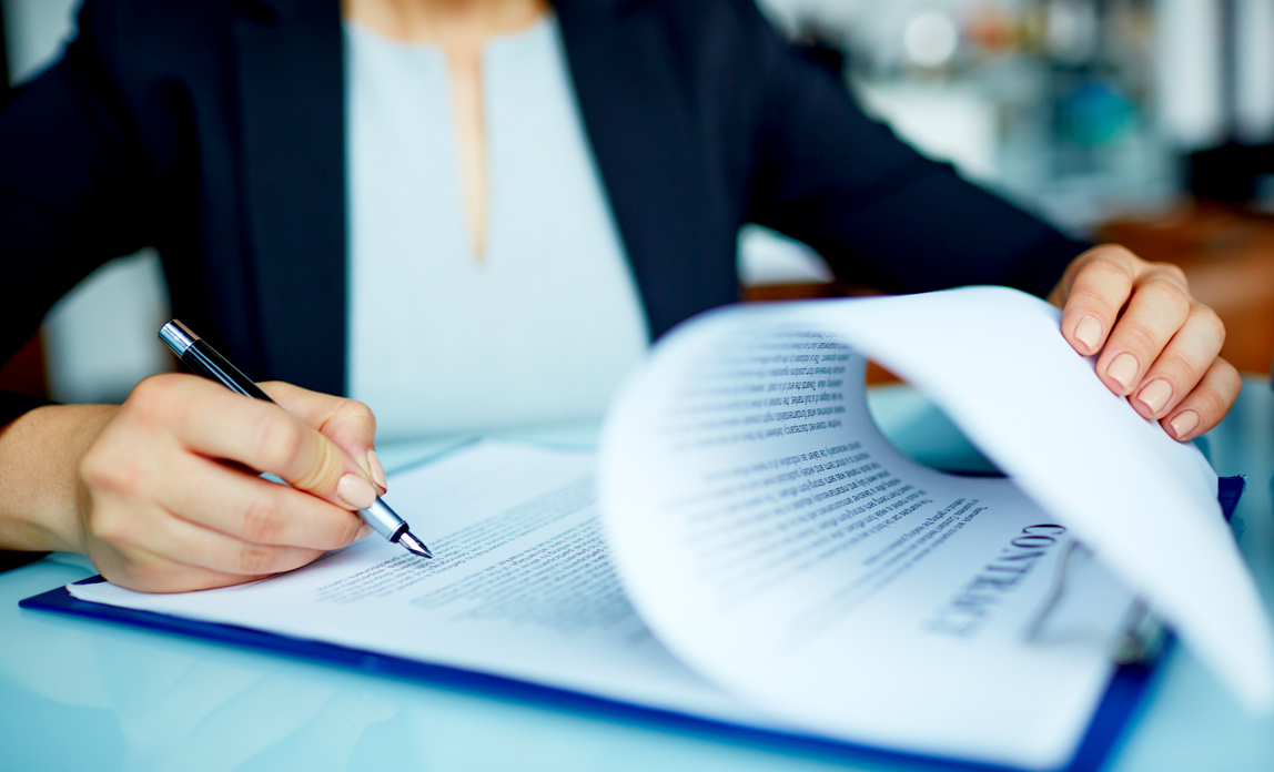 Woman signing papers - Selling a business FAQs
