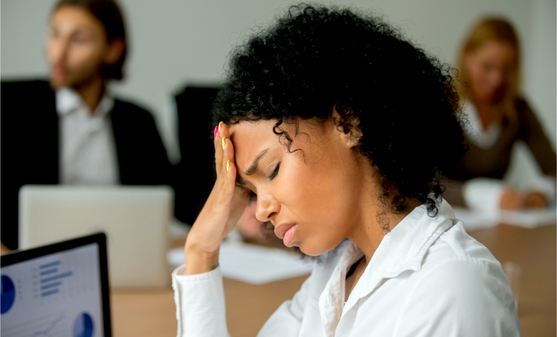 A worried employee holds her head and looks stressed in the workplace - money problems.